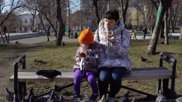 Una-mujer-joven-y-una-niña-comen-bollos-y-alimentan-palomas-en-un-día-frío-y-nublado-
