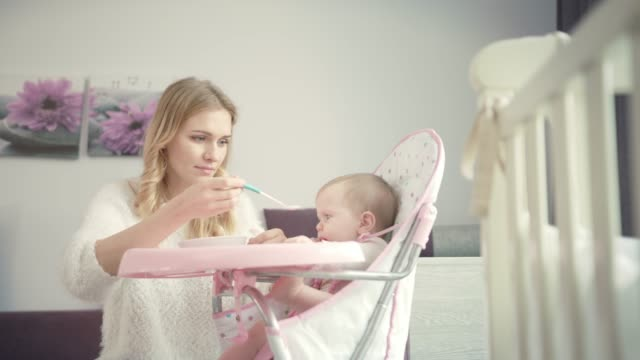 Beautiful-mom-try-feeding-baby-with-porridge-Infant-gnawing-teethers