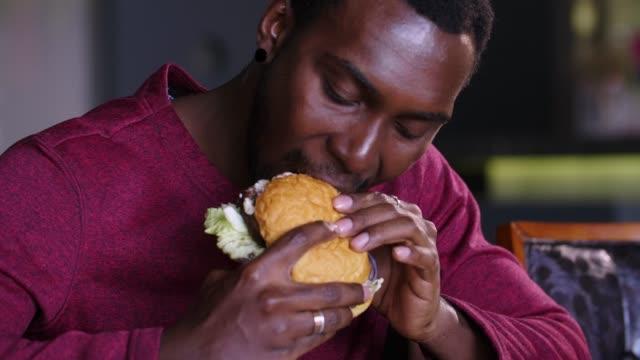 happy-fat-african-american-man-eating-a-hamburger-