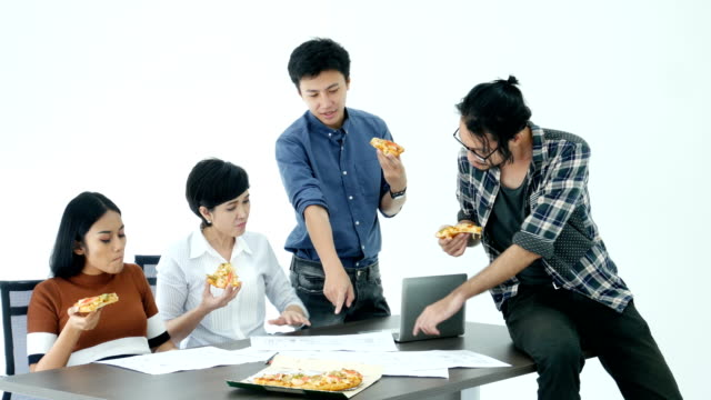 Asian-people-eating-pizza-while-work-at-office-together-people-working-concept-