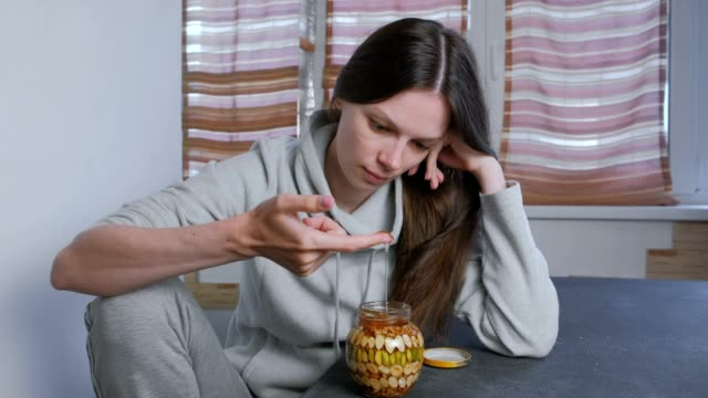 Woman-dips-her-finger-in-honey-with-nuts-in-the-jar-Eats-honey-from-finger-