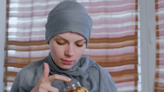 Muslim-woman-in-a-headscarf-dips-her-finger-in-honey-with-nuts-in-the-jar-Eats-honey-from-finger-