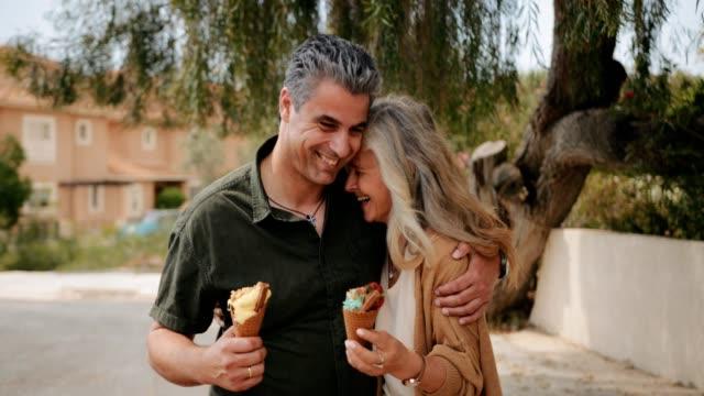 Feliz-pareja-multiétnica-comiendo-helado-en-primavera