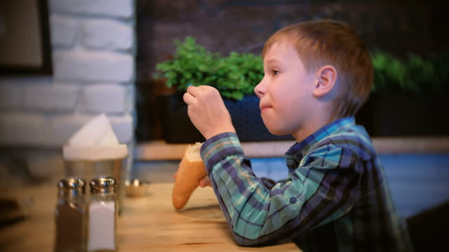 Boy-eats-a-baguette-and-watches-TV-in-the-cafe-Side-view-