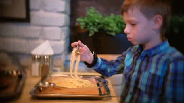 Niño-come-espaguetis-en-el-café-y-TV-de-relojes-