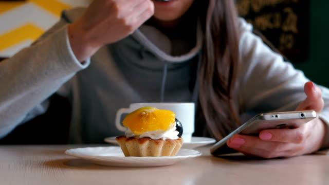 Mujer-irreconocible-come-una-torta-con-una-cuchara-y-mira-la-pantalla-del-teléfono-De-cerca-