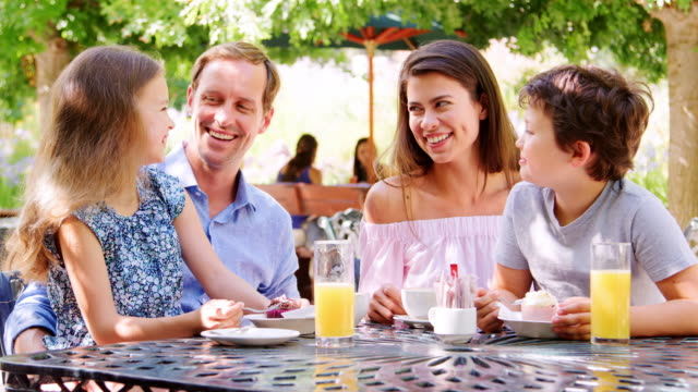 Parents-eating-outdoors-in-a-park-cafe-with-their-kids