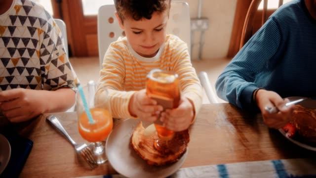 Niño-comiendo-panqueques-para-el-desayuno-con-los-hermanos-en-la-mañana