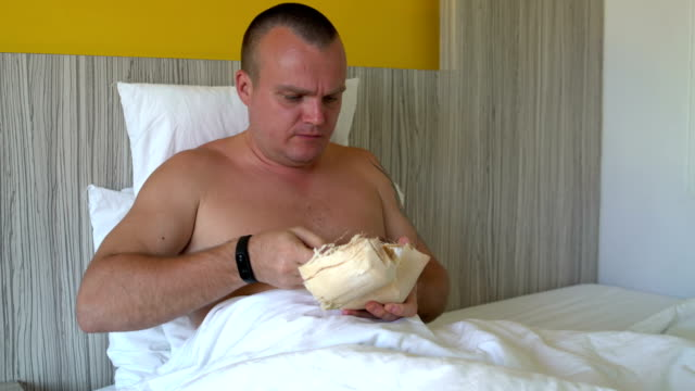 Man-lies-in-bed-eating-a-young-coconut-with-a-spoon