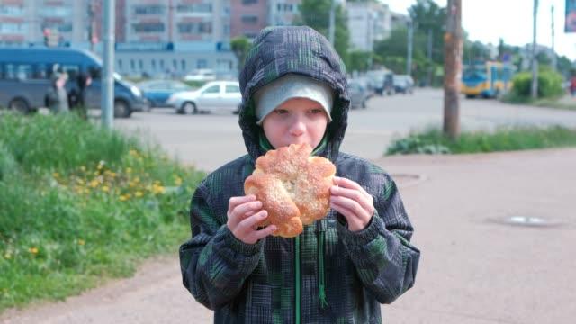 Boy-eating-a-bun-on-the-street-