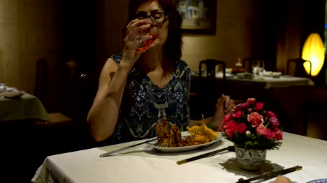 Woman-sitting-at-a-table-in-the-restaurant-eating-talking-chokaetsja-a-glass-and-drinking-red-wine