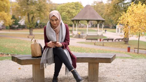 British-Muslim-Woman-Texting-On-Mobile-Phone-In-Park