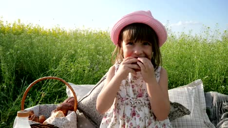 Lovely-girl-on-flower-meadow-with-basket-for-Picnic-female-child-in-panama-with-bun-on-nature-Weekend-at-picnic