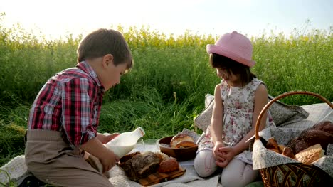 Children-and-nature-Friends-on-green-lawn-picnic-Boy-and-girl-with-food-on-nature-Happy-children-in-fresh-air-Boy-pours-milk