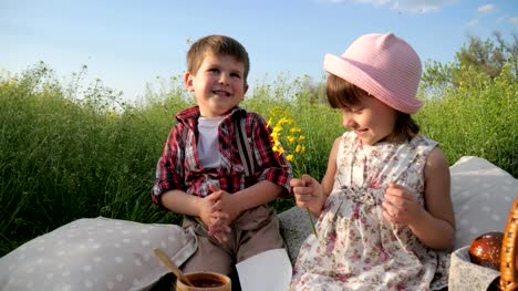boy-is-looking-at-beautiful-girl-closeup-portrait-boy-is-giving-flowers-to-pretty-girl-young-couple-in-love-two-adorable-children