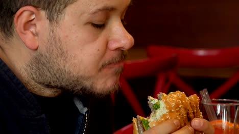 Hungry-man-bytes-a-big-burger-Close-up-on-man-eating-burger