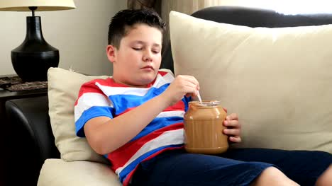 Young-boy-eating-peanut-butter