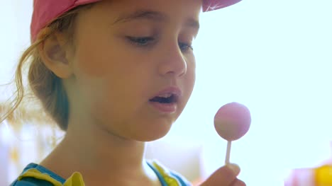 Little-girl-enjoying-a-lollipop-while-staring-at-camera-Child-eating-candy-sweets-sugar