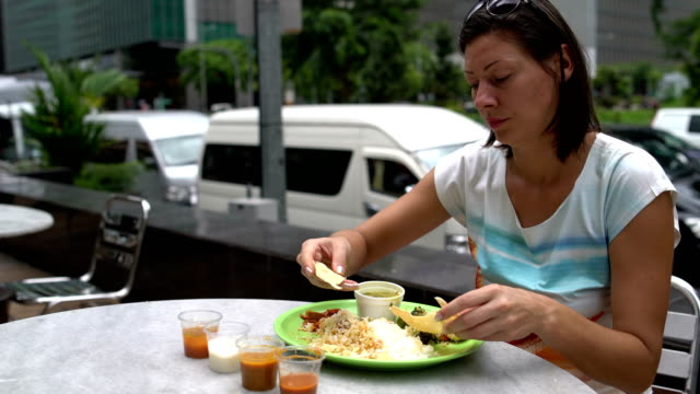 A-woman-breaks-a-traditional-Indian-cake-and-eats-thali-with-her-hands