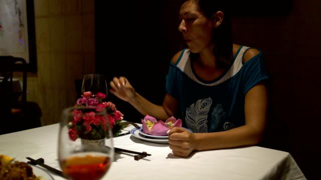Chica-sentada-en-una-mesa-en-el-restaurante-comer-hablar-chokaetsja-un-vaso-y-beber-vino-tinto