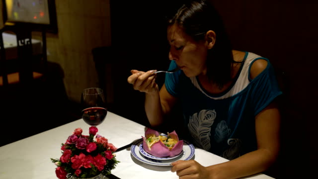 Chica-sentada-en-la-mesa-de-comer-de-plato-en-forma-de-una-flor-de-loto-y-beber-vino-tinto