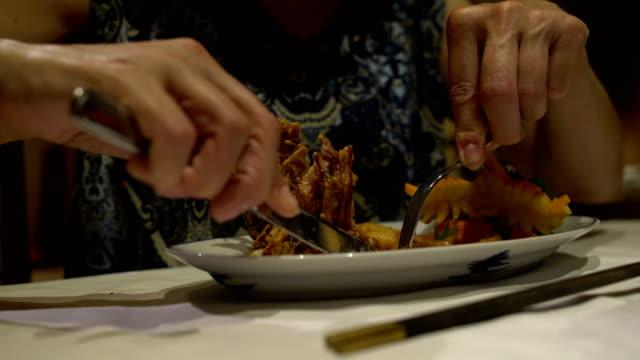 Manos-de-la-mujer-caucásica-con-un-cuchillo-y-el-tenedor-para-cortar-carne-en-masa