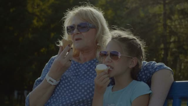 Kid-eating-eating-icecream-with-grandmother-outdoor