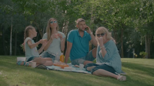 Positive-multi-generation-family-enjoying-picnic