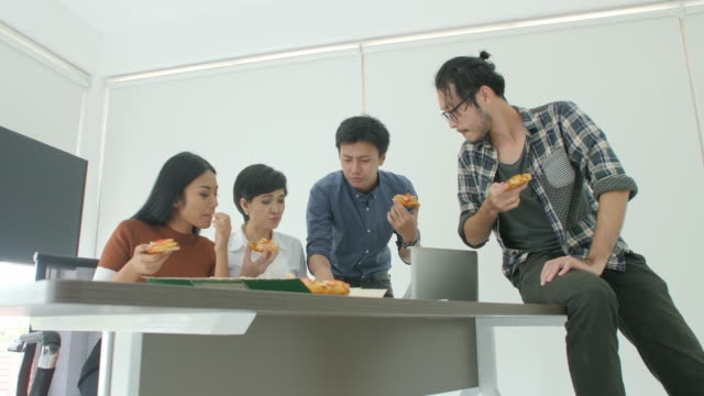 Casual-Creative-Business-team-having-lunch-while-meeting-in-office