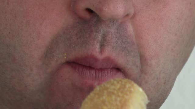Young-man-eating-hamburger-close-up