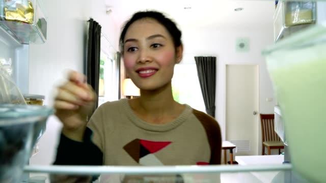 Refrigerador-abierto-de-mujer-buscando-recoger-arándanos-kiwi-y-yogurt