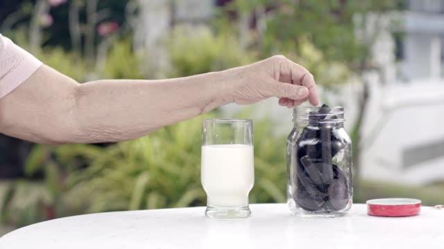 ältere-Menschen-hand-eintauchen-und-eine-Schoko-Cookie-In-Glas-Milch-rühren
