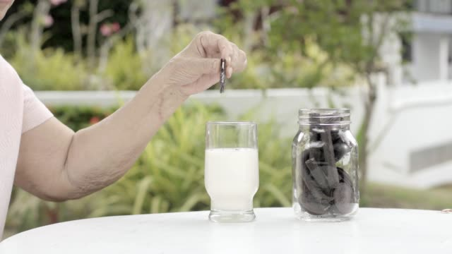 elderly-hand-dipping-and-stir-a-chocolate-cookie-In-milk-glass