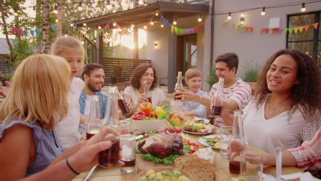 Familiares-y-amigos-reunieron-en-la-mesa-Levante-vidrios-y-botellas-para-hacer-un-brindis-y-tintineo-vasos-Celebración-fiesta-de-jardín-grande-de-la-familia-