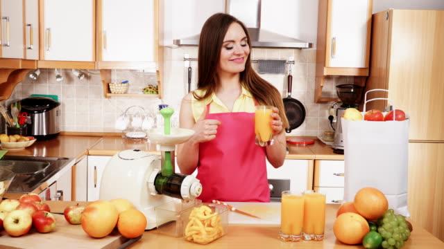 Mujer-en-la-cocina-bebiendo-zumo-de-naranja-4K