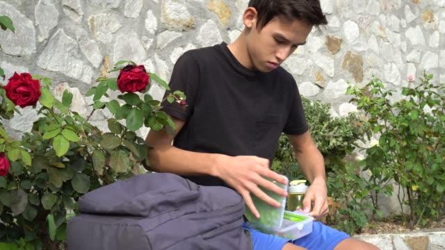 Un-estudiante-tiene-comida-en-el-patio-colegio-Parque