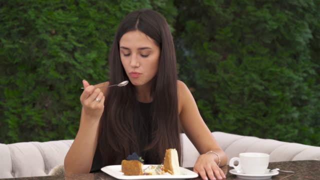 Un-primer-plano-de-una-bonita-morena-comiendo-un-pastel-en-una-terraza-Ella-come-un-pedazo-y-luego-toca-la-mejilla-sintiendo-un-dolor-de-muelas