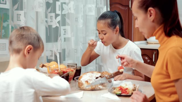 Family-dinner-Mom-daughter-and-son-have-dinner-together-in-the-kitchen