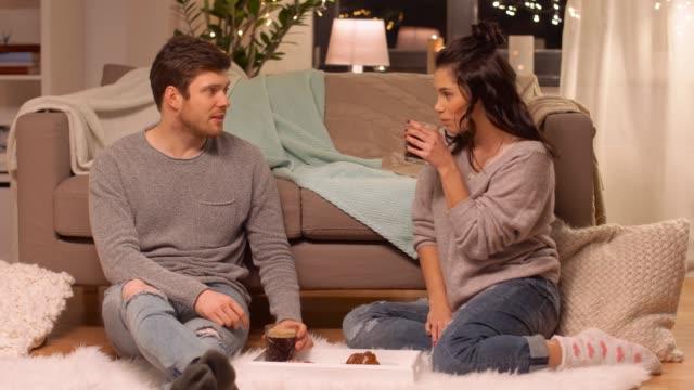 pareja-feliz-bebiendo-café-y-comiendo-pasteles-en-casa