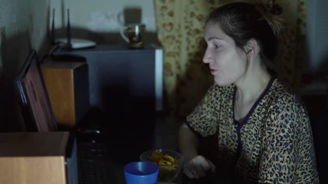 niña-mirando-la-película-en-la-computadora-y-comiendo-patatas-fritas-