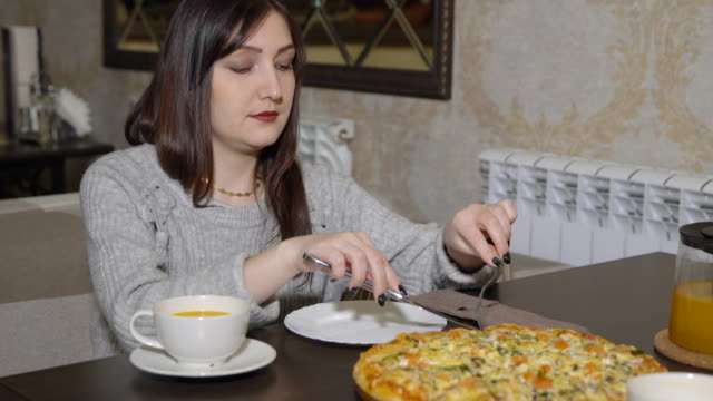 Pizzeria-Young-woman-takes-a-slice-of-pizza-with-cutlery