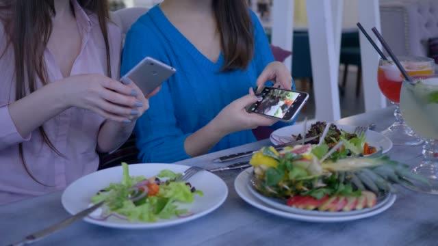 blogging-manos-de-amigas-toman-fotografías-de-comida-útil-hermosa-teléfono-móvil-durante-el-desayuno-en-la-dieta-para-bajar-de-peso-en-café