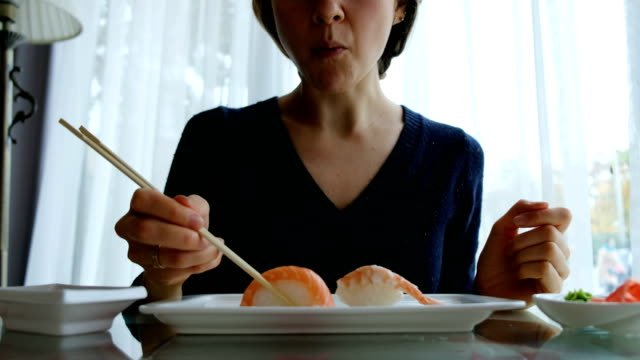 young-caucasian-girl-eating-sushi-in-Japanese-restaurant