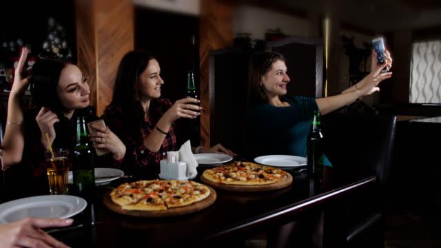La-compañía-de-chicas-alegres-en-la-pizzería-Chica-haciendo-un-selfie-con-un-smartphone-en-la-pizzería-