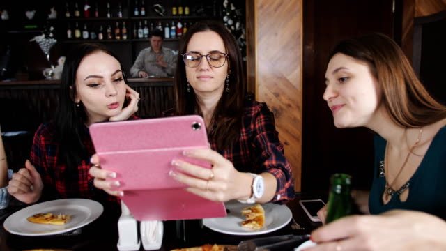 Four-girls-in-the-restaurant-viewing-photos-on-the-tablet-Pizza-and-beer-in-the-restaurant-