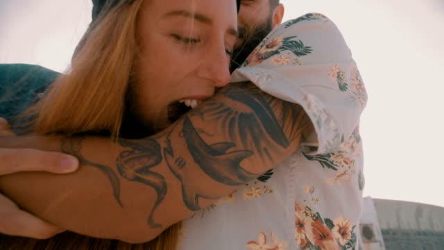 Hipster-girl-playfully-pretending-to-bite-her-boyfriend-s-tattooed-arm