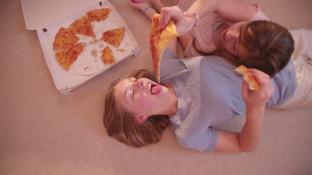 Girls-lying-on-the-floor-sharing-some-take-away-pizza