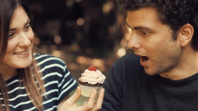 Junges-Mädchen-bietet-eine-süße-Himbeere-Cupcake-zu-Ihrem-Freund