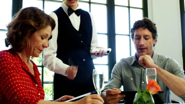 Cute-couple-ordering-form-the-menu-to-the-waitress