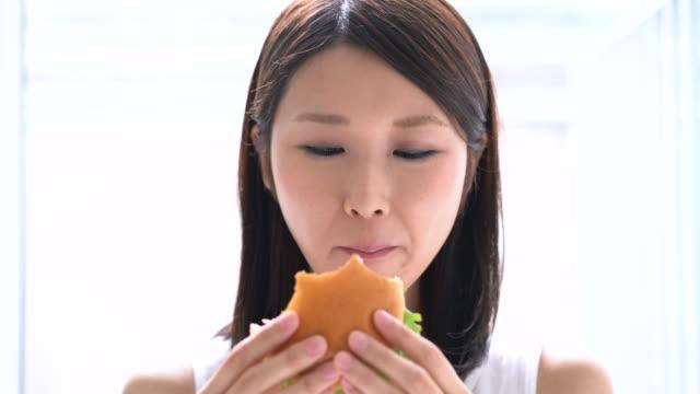 young-woman-eating-hamburger
